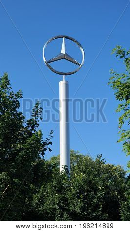 Large Mercedes-Benz Logo. Brussels, Belgium - June 2, 2017.  A tall Mercedes-Benz sign with the recognizable brand emblem stands above the trees at a dealership outside of Brussels