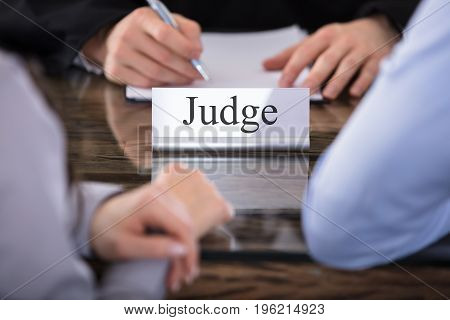 Close-up Of A Judge With The Name Plate Engraving Judge On Desk