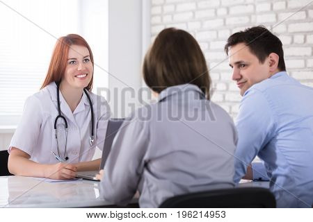 Rear View Of A Couple Sitting In Front Of Female Doctor