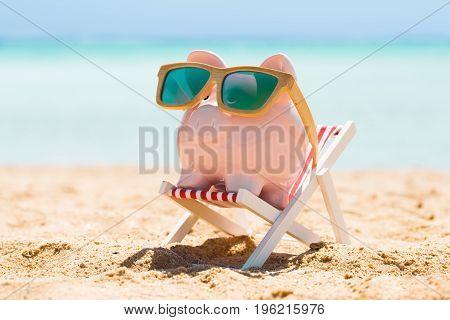 Pink Piggy Bank Wearing Wooden Sunglasses Kept On The Deck Chair At Beach