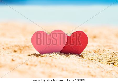 Two Pink And Red Hearts In Sand At Beach