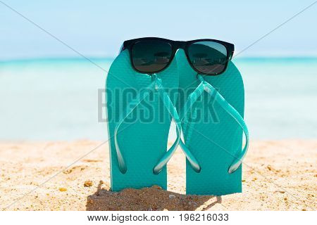 Sunglasses Over The Turquoise Flip Flop On Sand At Beach In Summer