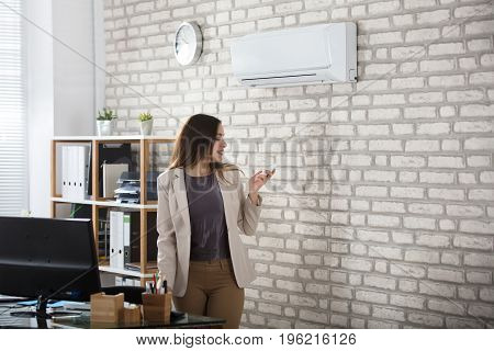 Young Businesswoman Standing In Office Using Remote Control Of Air Conditioner