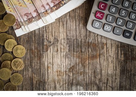 Coins and calculators on the old wood table,finance concept