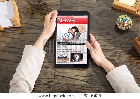 Woman Holding Digital Tablet With A Screen Showing Unfolds Scandal News Over The Wooden Desk