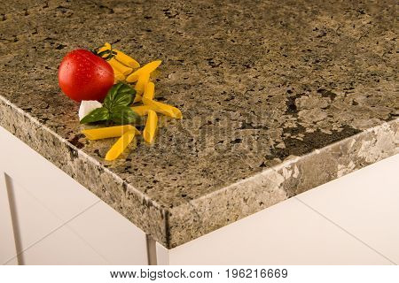 Granite countertop with greenish texture and white cabinet. Granite countertops. Kitchen granite countertops color samples. Modern kitchen countertops. Colorfull kitchen granite countertops squares. Countertops concept. Granite Stone.