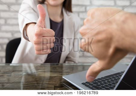 Close-up Of A Businesswoman Showing Thumbs Up To Her Colleague At Workplace In Office