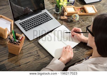 A Business Person Writing Down In Checkered Notebook With Black Marker Over The Desk