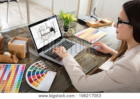 An Female Architect Working On Color Selection For The Kitchen Drawing On Laptop Screen