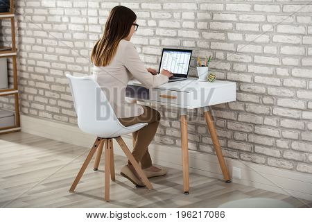 Close-up Of A Businesswoman Analyzing The Gantt Chart On Laptop In Office