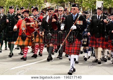 Victoria BC,Canada,May 10th 2014.Scottish mans marching bagpipe band march in unison at the Highland games parade in Victoria BC.Dressed in traditional Scottish attire with kilts ,tams and knee socks, and of course their bagpipes.