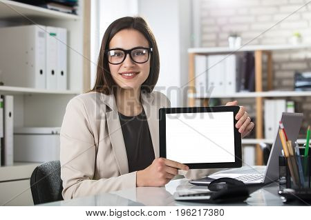 Close-up Of A Young Smiling Woman Showing Blank Screen On Digital Tablet At Workplace