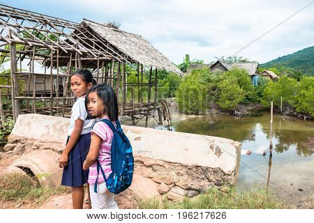 EL NIDO PALAWAN PHILIPPINES - JANUARY 20 2017: Two filipino girls going to school by foot in a beautiful local village in El Nido.