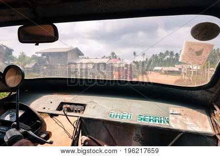 EL NIDO PALAWAN PHILIPPINES - JANUARY 20 2017: From the cockpit of a tuk tuk in a road. In front of the tuk tuk people walking with umbrellas in El Nido.