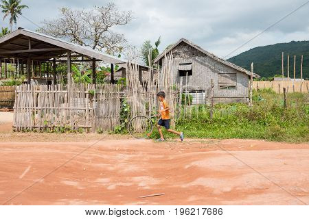 EL NIDO PALAWAN PHILIPPINES - JANUARY 20 2017: Filipino boy running and playing in a dirt road in El Nildo.