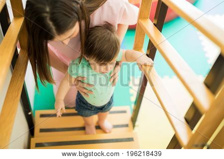 Woman Helping Baby Go Upstairs