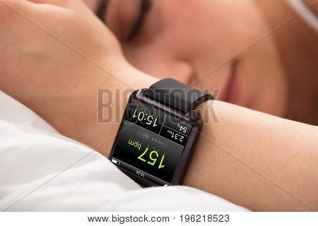 Smart Watch Showing Heartbeat Rate On Sleeping Woman's Hand