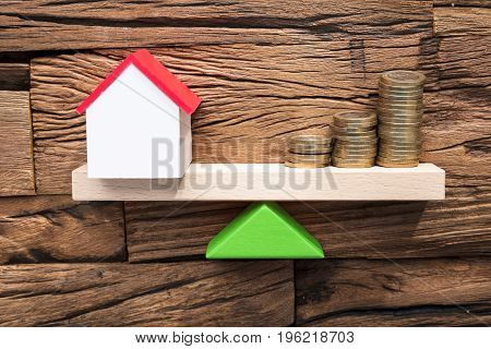 Closeup of stacked coins and model house balancing on seesaw against wood