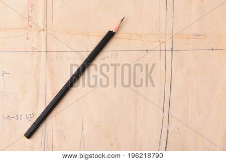Black pencil placed on a piece of cut paper.