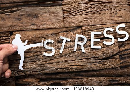 Closeup of hand holding paper businessman kicking word stress on wood