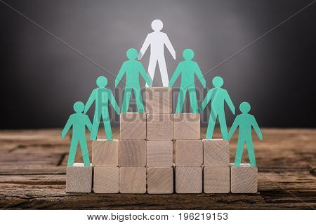 Closeup of paper boss with employees standing on wooden blocks