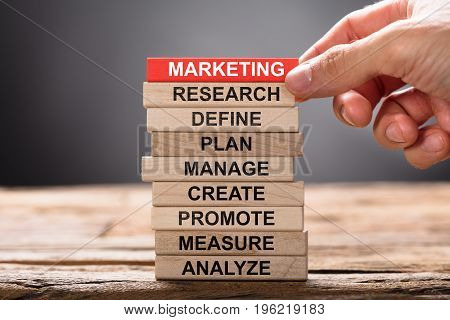 Closeup of hand building marketing concept with wooden blocks on wood