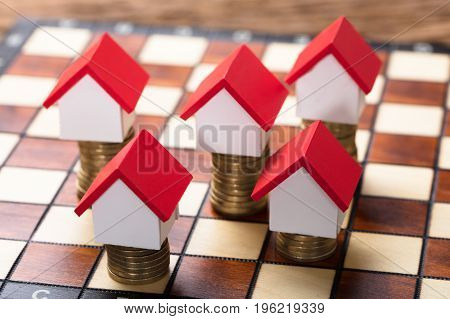 Closeup of house models on stacked coins on chessboard