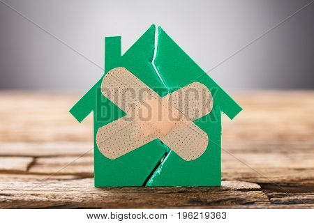 Closeup of broken house with crossed band aid on wood