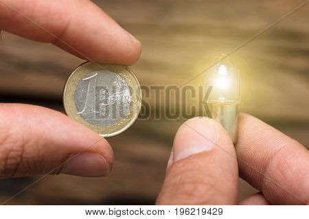 Closeup of hands holding one euro coin and lit lightbulb