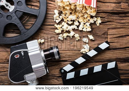 Closeup of movie camera with film reel clapper board and popcorn on wood