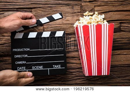Closeup of hands holding clapperboard by popcorn on wood