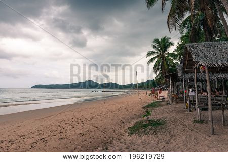 EL NIDO PALAWAN PHILIPPINES - JANUARY 20 2017: Back clouds over Nacpan Beach. Tourists under the tents waiting for better weather.