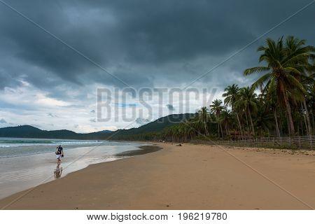 EL NIDO PALAWAN PHILIPPINES - JANUARY 20 2017: Lonely man walking at Nacpan Beach during cloudy day Philippines.