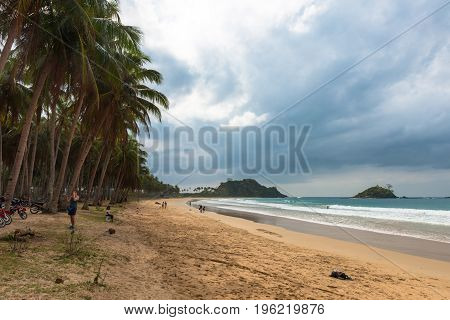 EL NIDO PALAWAN PHILIPPINES - JANUARY 20 2017: Horizontal picture of Nacpn Beach with some people in a blue sky day. Coconut trees yellow sand and waves in this tropical island.