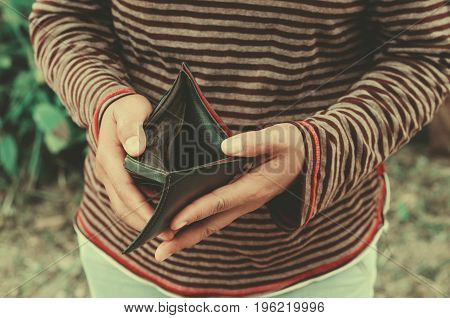 hipster woman holding an empty wallet she has no money