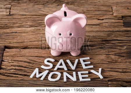 Closeup of piggybank by save money text on wooden table