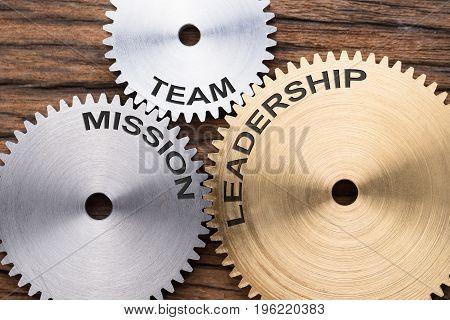 Closeup of team mission and leadership interlocked cogwheels on wood