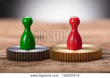 Closeup of red and green pawn figurines on interlocked cogwheels on wooden table
