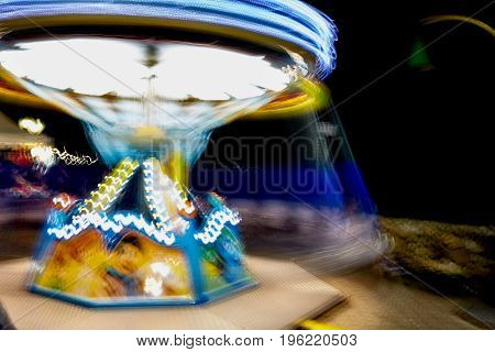 Long exposure of illuminated carousel in movement.