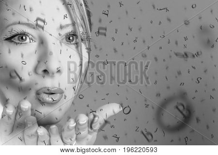 Young woman blowing in the air the letters of the alphabet educational concept black and white image.