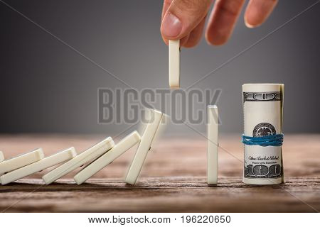 Cropped image of businessman's hand picking domino piece falling towards rolled dollar bills on table