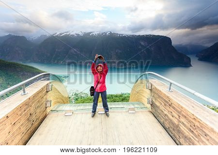 Tourism and travel. Woman tourist nature photographer taking photo with camera enjoying Aurland fjord landscape from Stegastein lookout Norway Scandinavia.