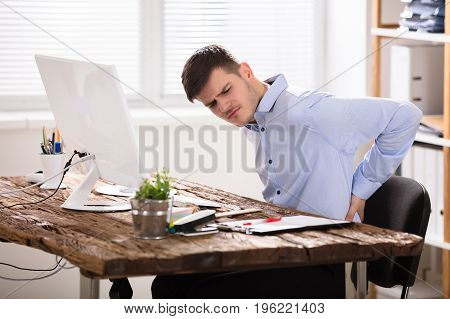 Sad Businessman Sitting On Chair Having Back Pain In Office