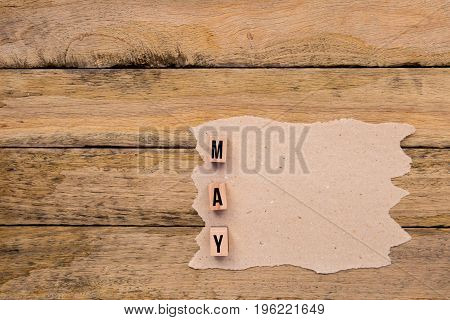 May - Calendar Month In Wooden Block Letters With Handmade Paper For Copy Space On Wooden Background