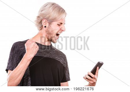 Technology and communication. Angry mad young man using mobile phone reading bad message isolated on white