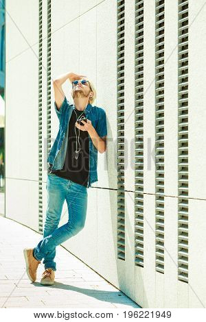 Men fashion technology urban style clothing concept. Hipster guy standing on city street wearing jeans outfit and sunglasses listening to music looking into sky