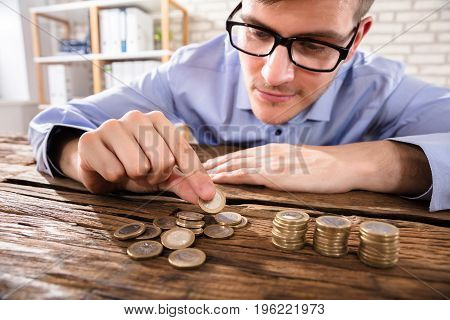 Close-up Of A Young Businessman Counting Coins Over Wooden Desk