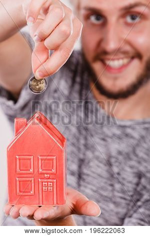 Household savings and finances economy concept. Smiling man putting money coin into piggy bank in shape of house studio shot on light background