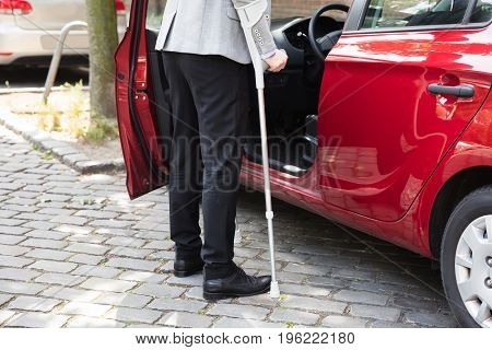 Disabled Person With Crutches Standing Near Open Door Of A Car