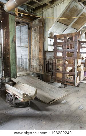 Inside vintage abandoned wool factory mill with wooden cart.